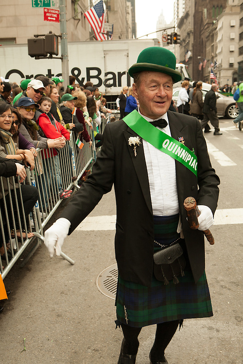 A man from Quinnipiac University,wearing a kilt and a green bowler hat, and carrying a shillelagh.