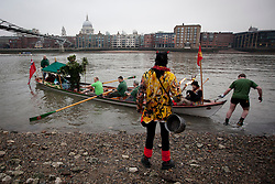 © Licensed to London News Pictures. 06/01/2013. London, UK. A member of the 'Bankside Mummers' dressed as 'Beelzebub' (foreground) waits for the 'Holly Man' to come ashore from the Thames during the annual 'Twelfth Night' Celebration in London today (06/01/13). The tradition, a pagan celebration of the new year and the end if Christmas, takes place every year at Bankside outside the Globe Theatre and sees the actors of the Bankside Mummers perform for the public. Photo credit: Matt Cetti-Roberts/LNP