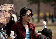 Fashion in North Korea<br /> <br /> In every corner of the earth, women love to look beautiful and keep up with the latest fashion trends. The women of North Korea are no different. Fashion is taken seriously here. But in North Korea, women do not read Elle or Vogue; they just glimpse a few styles by watching TV or by observing the few foreigners who come to visit. In the hermit kingdom, clothing also reflects social status. If you have foreign clothes it means you travel and are consequently close to the centralized power. Chinese products have inundated the country, adding some color to the traditional outfits that were made of vynalon fiber. But citizens beware, too much style means you're forgetting the North Korean juche, the ethos of self-reliance that the country is founded on! But the youth tend to neglect it despite the potential consequences.<br /> <br /> Photo shows: The elite can travel in North Korea. Many go to China or Europe and return with new trendy clothes. This lady with Christian Dior glasses may be part of this upper echelon. The clothes North Koreans wear signify their economic status.<br /> ©Eric Lafforgue/Exclusivepix Media