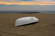 A solitary life boat on the beach early in golden light of  morning