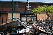 Charred and damaged items line the street outside Migizi, a local non-profit devoted to the development of Native American youth along Lake Street in Minneapolis, Minnesota on Monday, June 1, 2020.