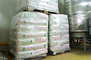 Piles of 50 kilo sacs wrapped in plastic film on pallets of refined cane sugar (sucre raffine pure canne) that is widely used in wine and champagne production e.g. to induce the secondary fermentation in bottle at Champagne Deutz in Ay, Vallee de la Marne, Champagne, Marne, Ardennes, France