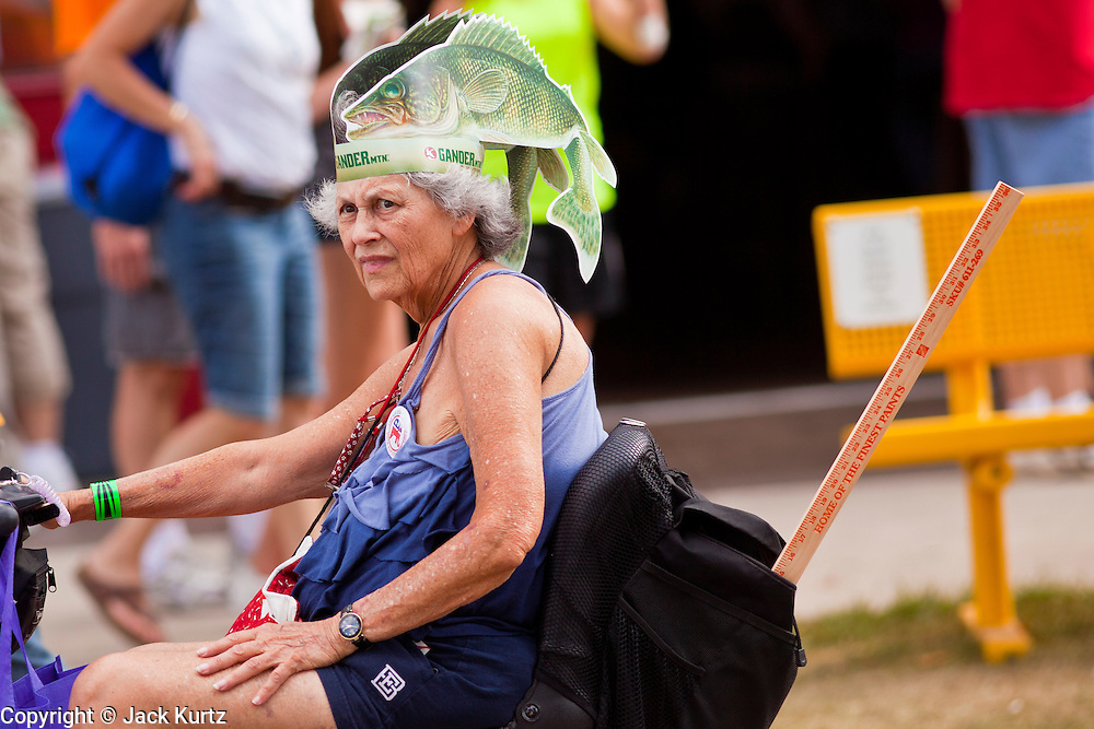 """01 SEPTEMBER 2011 - ST. PAUL, MN:  A woman wearing fish hat from Gander Mountain, a Minnesota based sporting goods chain, rides through the fair grounds at the Minnesota State Fair. The Minnesota State Fair is one of the largest state fairs in the United States. It's called """"the Great Minnesota Get Together"""" and includes numerous agricultural exhibits, a vast midway with rides and games, horse shows and rodeos. Nearly two million people a year visit the fair, which is located in St. Paul.   PHOTO BY JACK KURTZ"""