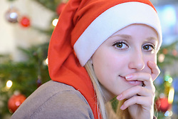 Portrait of teenage girl in front of christmas tree