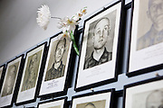 Framed photographs of male camp inmates with flower offering, Auschwitz, Poland.
