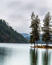 A man takes in the serenity of a spring storm at Fernan Lake in Coeur D'Alene Idaho