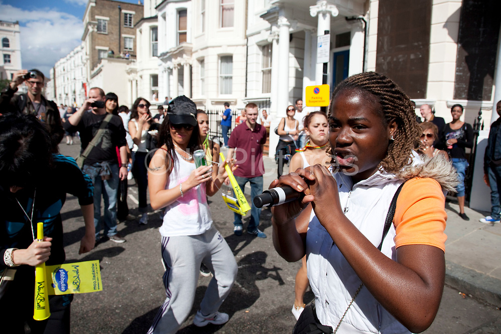 Dancing to live rappers at the Notting Hill Carnival in West London. The Notting Hill Carnival is an annual event which since 1964 has taken place each August, over two days (the August bank holiday Monday and the day beforehand). It is led by members of the West Indian / Caribbrean community, particularly the Trinidadian and Tobagonian British population, many of whom have lived in the area since the 1950s. The carnival has attracted up to 2 million people in the past, making it the second largest street festival in the world. The celebration centres around a parade of floats, dancers and sound systems.