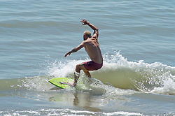 © Licensed to London News Pictures 14/06/2021. Folkestone, UK. A surfer surfing the waves. The hot heatwave weather continues today in Kent as people enjoy Sunny Sands beach in Folkestone. Photo credit:Grant Falvey/LNP