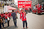 """Mar. 27, 2010 - BANGKOK, THAILAND:  A Red Shirt stands in the middle of a Bangkok street as other Red Shirts march past him Saturday, March 27. More than 80,000 members of the United Front of Democracy Against Dictatorship (UDD), also known as the """"Red Shirts"""" and their supporters marched through central Bangkok March 27 during a series of protests against and demand the resignation of current Thai Prime Minister Abhisit Vejjajiva and his government. The protest is a continuation of protests the Red Shirts have been holding across Thailand. They support former Prime Minister Thaksin Shinawatra, who was deposed in a coup in 2006 and went into exile rather than go to prison after being convicted on corruption charges. Thaksin is still enormously popular in rural Thailand.    PHOTO BY JACK KURTZ"""