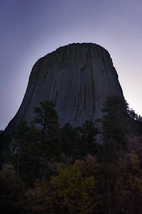 Devils Tower is framed by an obscured full moon and the last of the fall leaves at the base of the monument. Located in Northeast Wyoming, Devils Tower was the first declared National Monument in the United States, established in 1906 by President Theodore Roosevelt.