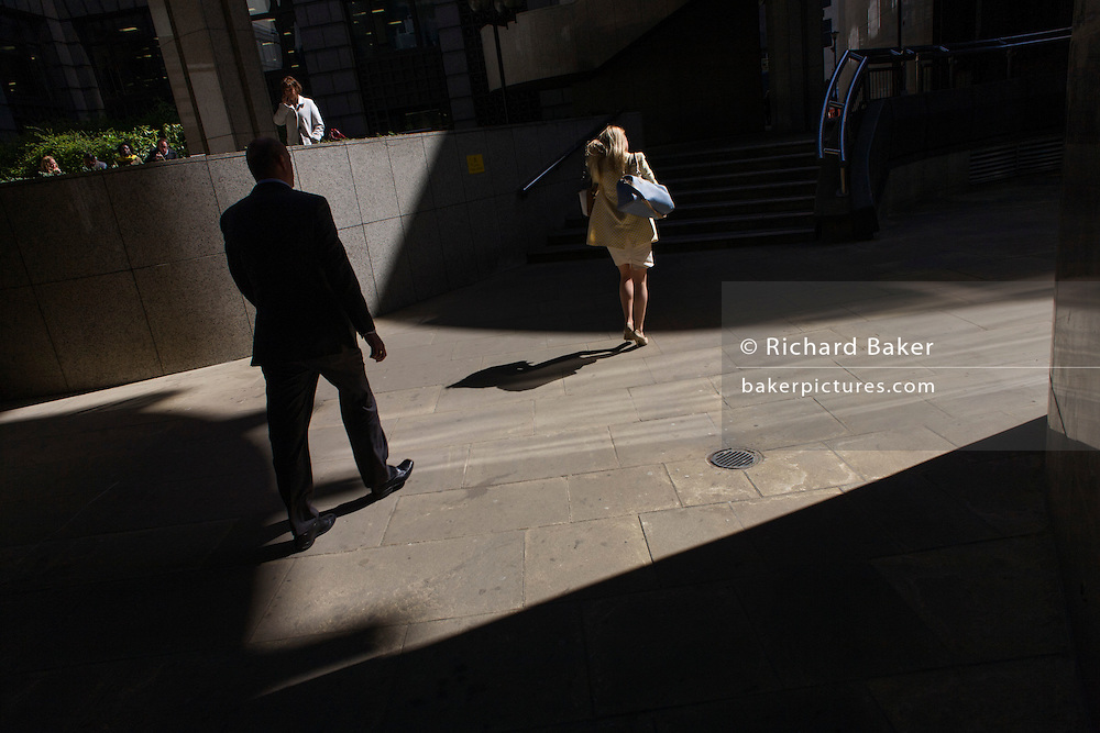 Silhouette of man follows woman through area of City of London sunlight