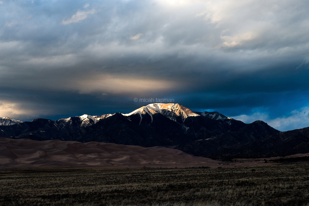 Sunset light reflects off the Sangre de Cristo mountains and lights the clouds over Great Sand Dunes National Park in Colorado.