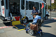 """Nofomuli Finaulahi helps Bruce Oka onto the San Francisco Paratransit Bus the """"Grayce Reagan"""" in front of the Ferry Building on the Embarcadero"""