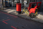 Parked at the kerbside on the Commecial Road Red Route in afternoon sunlight, are a red rickshaw vehicle alongside a red Royal Mail postal box on 21st October 2021, in London, England.