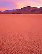 """CADDV 022 -   Sunrise reflects off clouds and turns dry lakebed or playa called """"Racetrack"""" shades of mauve, Racetrack Valley, Death Valley National Park, California, USA"""
