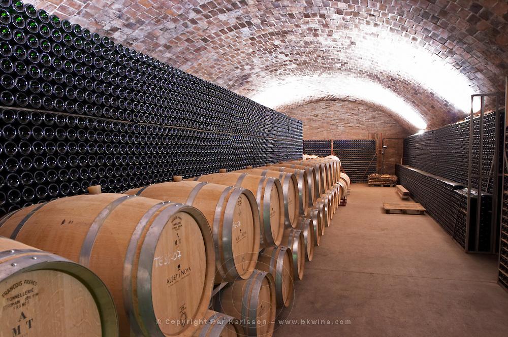Oak barrel and bottle aging cellar. Bottles stacked high in the cellar for aging. Albet i Noya. Oak barrel aging and fermentation cellar. Penedes Catalonia Spain