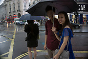 London, UK. Sunday 23rd August 2015. Heavy summer rain showers in the West End. People brave the wet weather armed with umbrellas and waterproof clothing. Chinese couple underneath an umbrella take pictures at Piccadilly Circus.