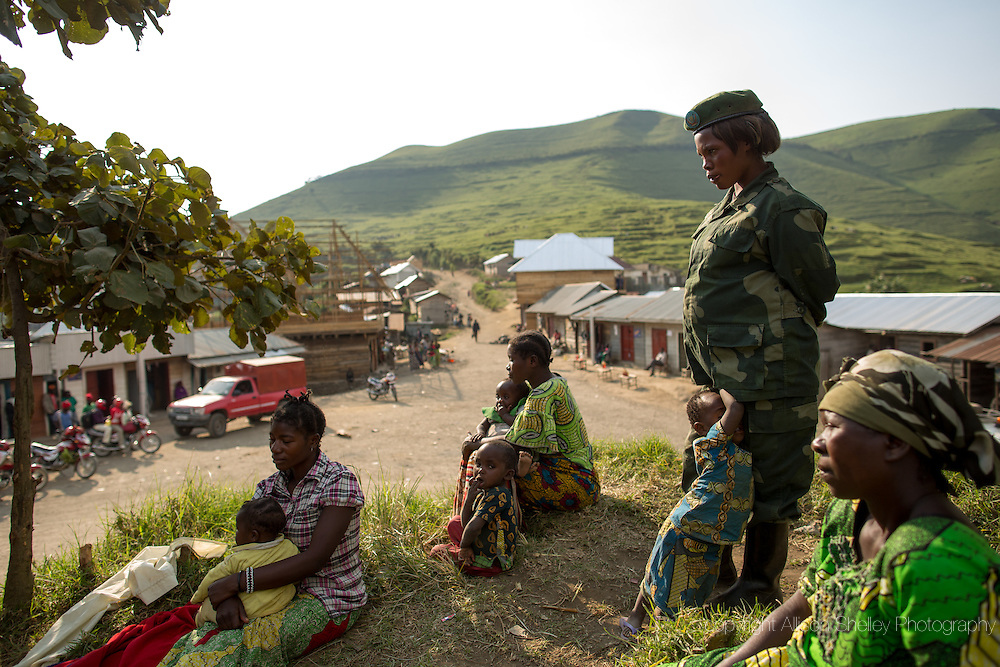 """First Sergeant Zawadi Bati, 27, a member of the Democratic Republic of Congo's army, the FARDC, stands guard with her two-year-old daughter Dorcas, who follows her to her posts, in the village of Mushake in North Kivu, Democratic Republic of Congo, July 31, 2014. Zawadi is seven months pregnant with her second child.  She gave birth to her after marching with her unit for several days to a village called Kigulube.  Within three of the birth the unit moved again, along with Zawadi and baby Dorcas.  """"As I was walking I didn't feel it, I had my mind set up like a soldier, I was just walking with my gun."""" Zawadi says that the father of her second baby died six months ago after being struck by lightening.  He was also a soldier."""