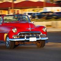 Central America, Cuba, Havana. Classic Car driving on the Malecon.
