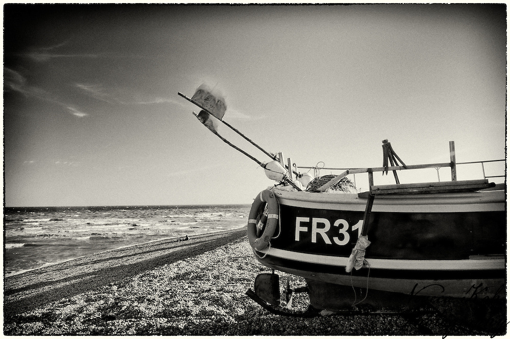 Boat with flags on the shingle beach at Dungeness, Kent, United Kingdom