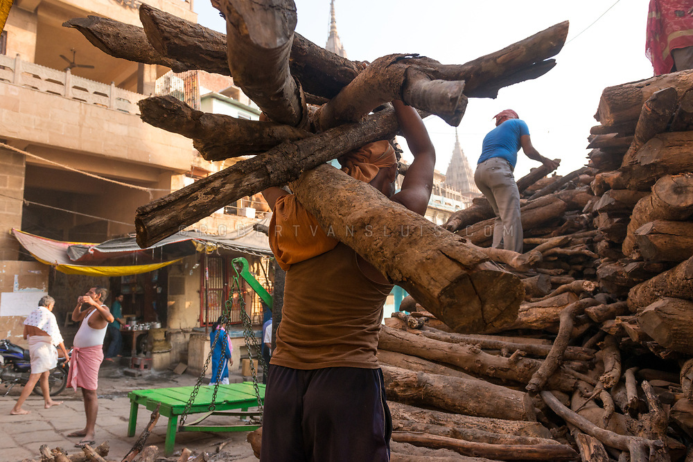 A man carries a supply of firewood near Manikarnika cremation ground, Varanasi, India. Photo © robertvansluis.com