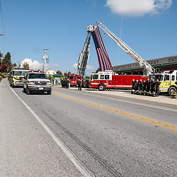 Peach Bottom, PA, USA - October 30, 2014: The funeral procession of fire apparatus for a fallen volunteer firefighter drives slowly past the Robert Fulton Fire Company in Lancaster County.