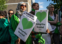 © Licensed to London News Pictures. 14/06/2018. London, UK. People join the silent procession at Grenfell Tower to mark the first anniversary of the Grenfell Tower Fire in which 72 people were killed. Grenfell Tower caught fire on the night of June 14, 2017 after a small blaze started in one of the flats which spread rapidly up the outside of the 24-floor tower block. A public inquiry is currently underway. Photo credit: Rob Pinney/LNP