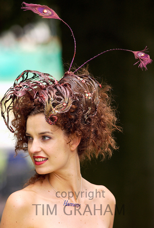 Race-goer wearing a hat which blends in with her hair at Royal Ascot Races. Her necklace has the word 'Harmony'