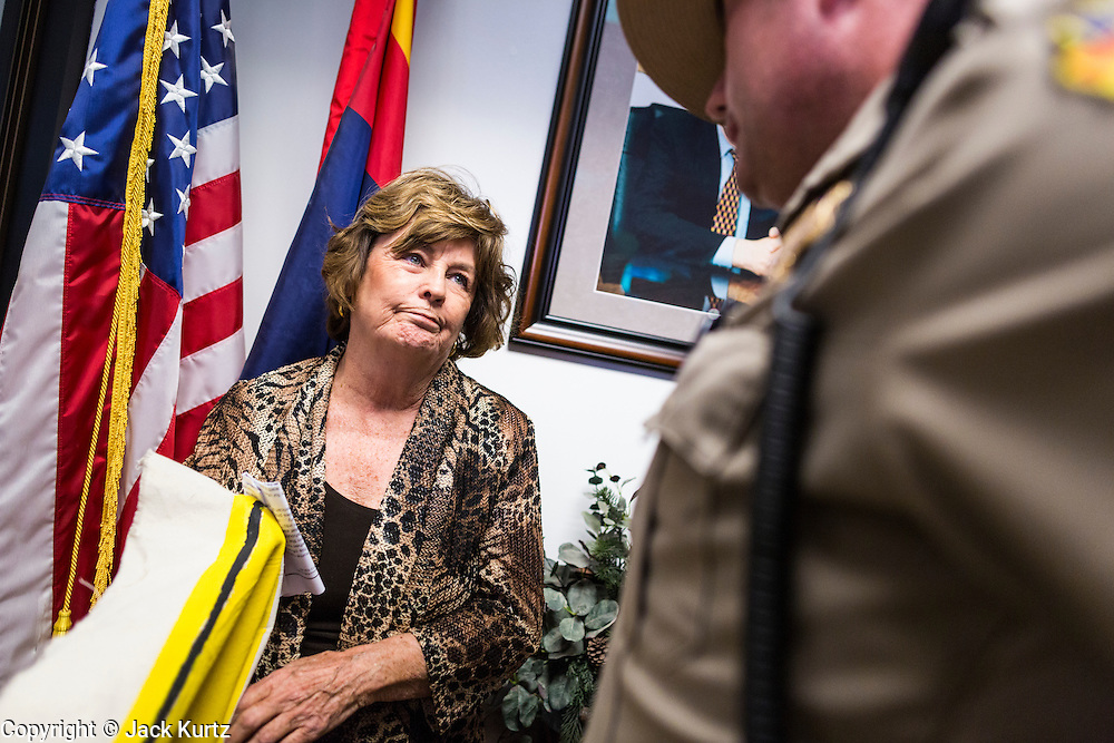 17 OCTOBER 2013 - PHOENIX, AZ:     CAROLYN O'CONNOR, formerly the Vice President of Student Affairs at Gateway Community College, is arrested by Arizona Capitol Police in the office of the Attorney General. About 100 people came to the office of Arizona Attorney General Tom Horne to protest the decision by Horne to sue community colleges in Maricopa County that charge DREAM Act students who are residents of Arizona out of state tuition rather than in state resident tuition. Nearly 10 people were arrested in a planned civil disobedience during the protest.   PHOTO BY JACK KURTZ