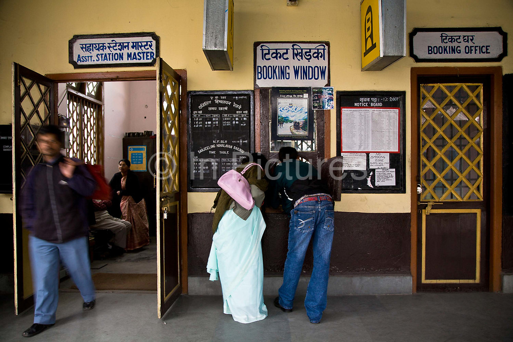 """Passengers buy ticket for the the daily run from Kurseong back to Darjeeling. The Darjeeling Himalayan Railway, nicknamed the """"Toy Train"""", is a narrow-gauge railway from Siliguri to Darjeeling in West Bengal, run by the Indian Railways. It was built between 1879 and 1881 and is about 86 km long. The elevation level is from about 100 m at Siliguri to about 2200 m at Darjeeling. It is still powered by a steam engine and travels daily between the two towns.  It is now classed as a World Heritage Site by UNESCO. India."""