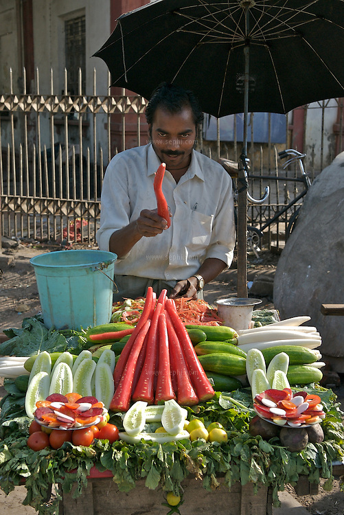 A vegetable vendor near Lahori gate in Old Delhi. Fresh vegetable seasoned with Chaat masala and black salt are eaten seperately or as a mixed plate as veg or fruit chaat, sometimes mixing fruit and vegetables in the same plate