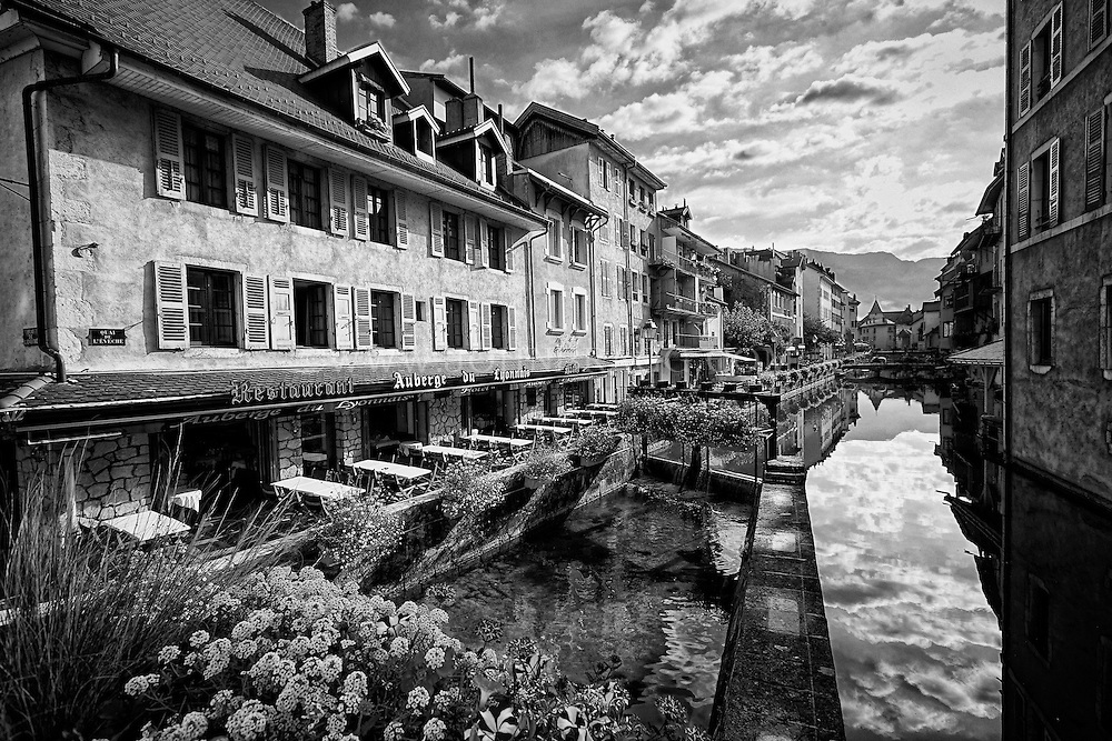 Black and white view of the Auberge du Lyonnais Hôtel/Restaurant and other buildings along the incredible reflective waters of the Thiou Canal, Old Town Annecy, France.