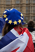 Anti Brexit pro Europe demonstrator with an EU flag beret protests waving European Union and Union Jack flags in Westminster opposite Parliament on the as five days of Brexit debate begins on 4th December 2018 in London, England, United Kingdom.