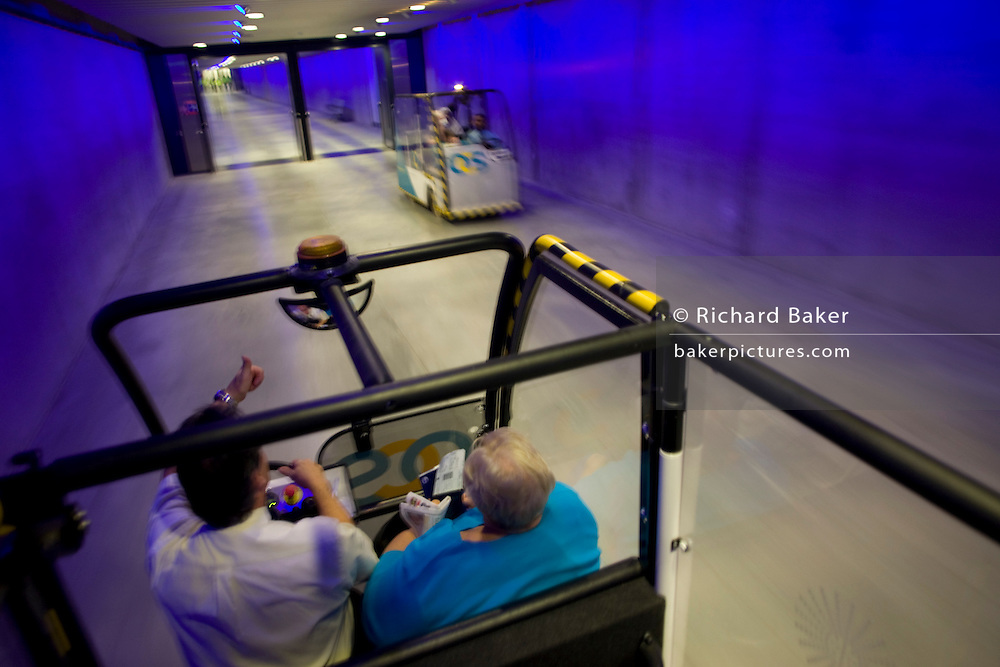 Infirm and elderly transit passengers transported through tunnel by buggy through Heathrow airport's terminal 5