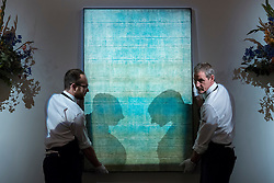 "© Licensed to London News Pictures. 13/10/2016. London, UK. Sotheby's technicians show ""Untitled, 1973"" by Vasudeo S. Gaitonde (est. GBP 0.9-1.4m) at the preview of Sotheby's Art of the Middle East and India exhibition, which presents artworks to be sold in New Bond Street in four sales in October. Photo credit : Stephen Chung/LNP"