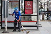 A cleaner wearing face protective shield sweeps the floor by a bus stop nearby Royal Courts of Justice in Central London on Friday, July 24, 2020, as the new rules on wearing masks in England have come into force, with people going to shops, banks and supermarkets now required to wear face coverings. <br /> Authorities said that Police can hand out fines of 100 pounds if people refuse, but authorities are hoping that peer pressure will prompt compliance. (VXP Photo/ Vudi Xhymshiti)