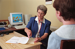 Doctor in community paediatric health centre sitting at desk wearing stethoscope around her neck; looking through medical notes and talking to patient,