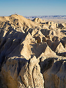 A couple sits on the dirt, talking and taking in the views. View of Badlands National Park on an early spring day; South Dakota, USA.