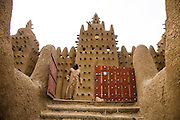 Djenné, Mali 2009 - A man exits the Great Mosque. It is the largest mud brick building in the world and was designated a World Heritage Site by UNESCO in 1988