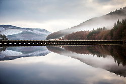 © Licensed to London News Pictures. 03/02/2021. Derwent UK. The hills that surround Ladybower reservoir in Derbyshire reflect into the calm water this morning.. Photo credit: Andrew McCaren/LNP