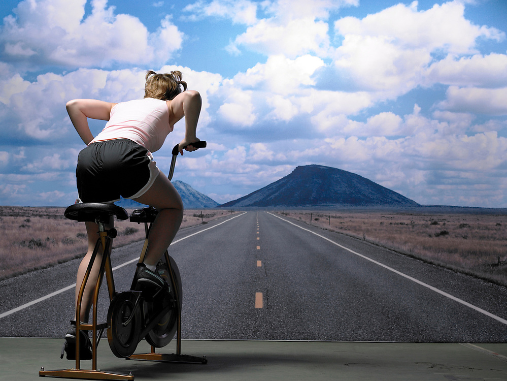 Young woman riding exercise bike in front of desert highway photograph