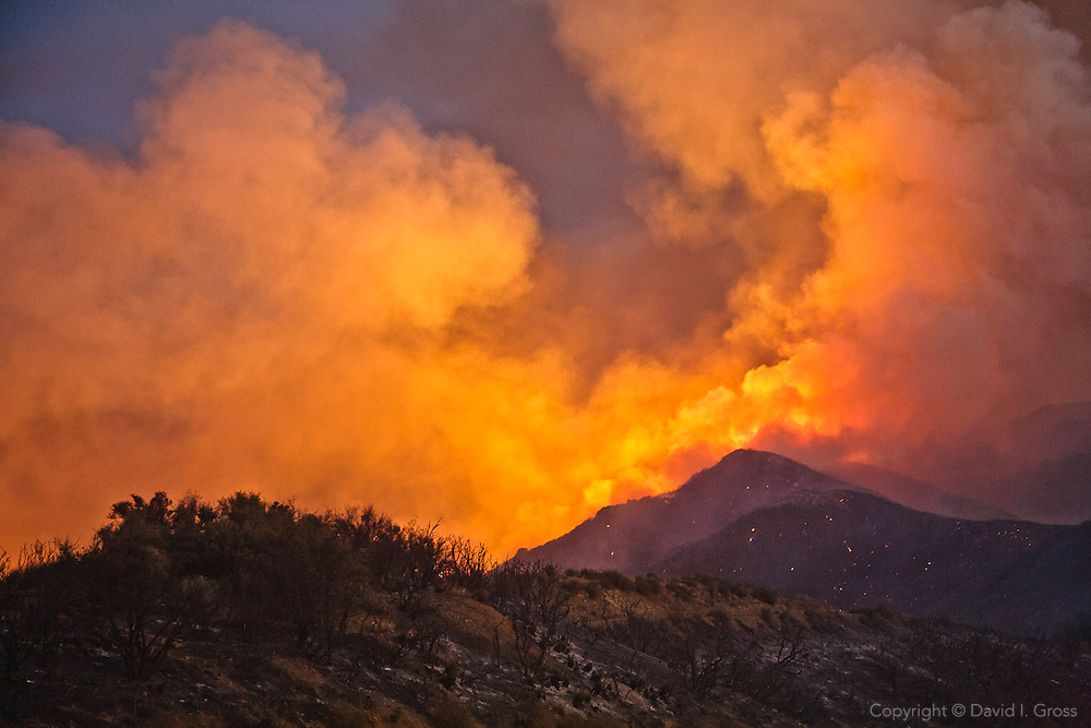 Glowing smoke fills the sky and sparkling embers dot the hills as night settles on the La Brea Fire in the Los Padres National Forest, California.