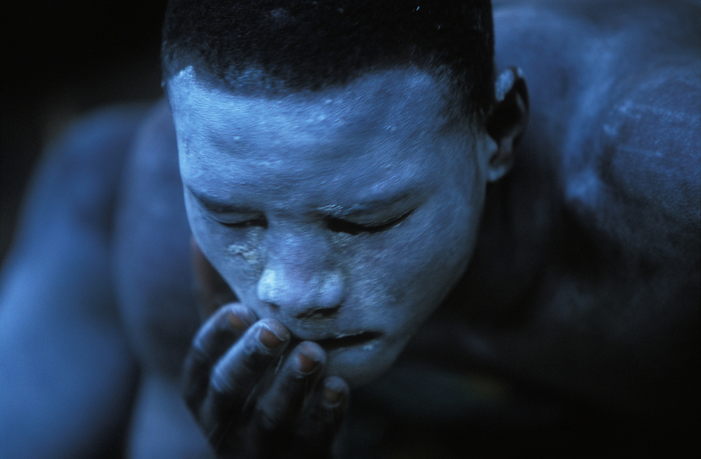 Young Xhosa initiate, who is going through the traditional Xhosa male initiation rite, is painting his face with white clay to ward of attacks by witches. December 2006 in Knysna, South Africa. He has been circumcised and is now spending a month in a special initiation camp just outside the township Khayalethu South.