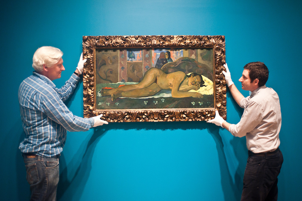 London, UK - 19 June 2013: Graeme Barraclough. Chief Conservator (L) and an art technician called Jack (R) work on a canvas entitled ?Nevermore 1897? by Paul Gauguin