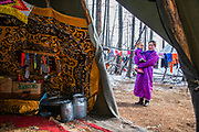 The view from inside of a teepee to the outside of Tsaatan reindeer herder mother holding her little daughter  in her arms, Khovsgol Province, Mongolia