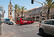 The red open roof tourist bus for sightseeing the city. passes the Jaffa clock tower
