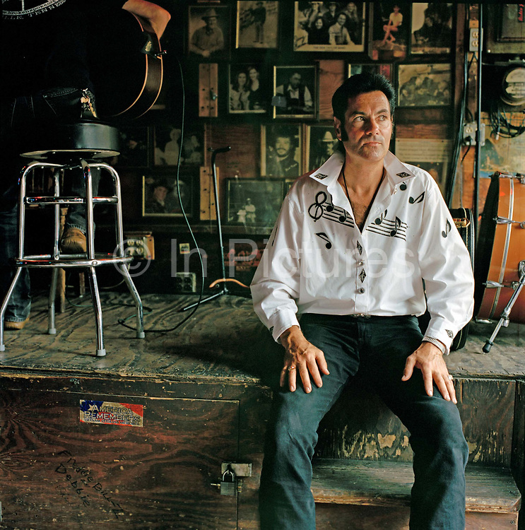 """Johnny Ville pictured here inside the world famous Tootsies bar on  Broadway has come to Nashville to develop his musical career. Nashville  is the Hollywood of Country Music and wannabe stars from all over the world flock there to make their fortune.  Johnny is a natural performer and self promoter """"Elvis was my daddy"""" he claims and promises to buy us a Cadillac when he is famous),  Johnny doesn't have a permanent address and seems to rove around trying to make a few bucks with his guitar. It seems the romantic spirit of Nashville is alive and well. Today There is still some great music to be found in Nashville  but one has to navigate some typical US commercialism in the search as  the town cashes in on its reputation."""