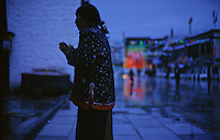 A pilgrim prays in the evening in front of the Jokhang temple, the most sacred site in Tibetan Buddhism. Lhasa, Tibet.