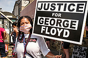 """15 AUGUST 2020 - MINNEAPOLIS, MINNESOTA: A woman at the George Floyd Memorial in front of Cup Foods in Minneapolis. Floyd, an unarmed Black man, was killed by Minneapolis police officers of May 25 in front of Cup Foods, a convenience store at the intersection of 38th and Chicago Ave. His killing sparked a week of violent protests across the country. The intersection where he was killed is still closed and has become an unofficial memorial visited by hundreds of people every day. Saturday, more than 100 people gathered at the memorial to demand the city preserve the memorial. On Saturdays in August, the intersection has a market, with venders selling Afro-centric merchandise. The city of Minneapolis had planned to start reopening the intersection as soon as Monday Aug. 17, but delayed those plans indefinitely on Friday, Aug. 14. City residents have created a """"George Floyd Zone"""" at the intersection. They're demanding the recall of Hennepin County Attorney Mike Freeman, requiring Minneapolis police officers have their own private liability insurance, and the allocation of funds for businesses and residents in the community. The city is considering officially renaming Chicago Ave. between 37th and 39th """"George Floyd Jr. Place.""""     PHOTO BY JACK KURTZ"""