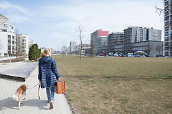 Rear view of woman walking on sidewalk with dog and suitcase, Munich, Bavaria, Germany